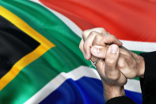 South Africa flag and praying patriot man with crossed hands. Holding cross, hoping and wishing.