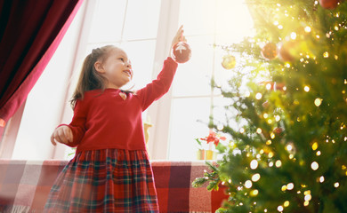 child with baubles near tree at home.