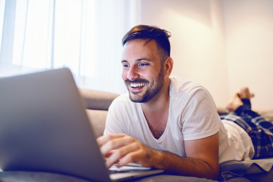 Joyful caucasian man in pajamas lying on stomach on sofa in living room and surfing on internet.