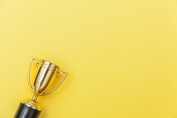 Simply flat lay design winner or champion gold trophy cup isolated on yellow colorful background. Victory first place of competition. Winning or success concept. Top view copy space