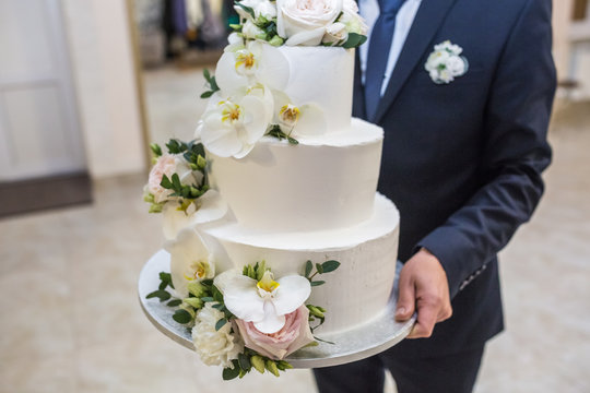 the groom carries a festive wedding cake decorated with white roses