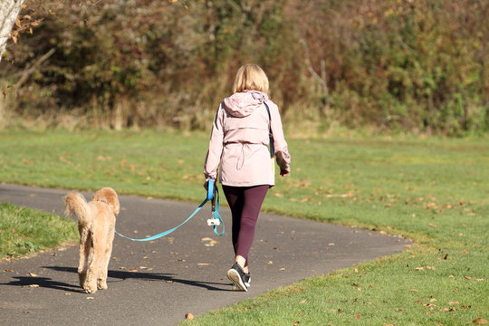 Adult woman walking her dog at the park on a sunny day.