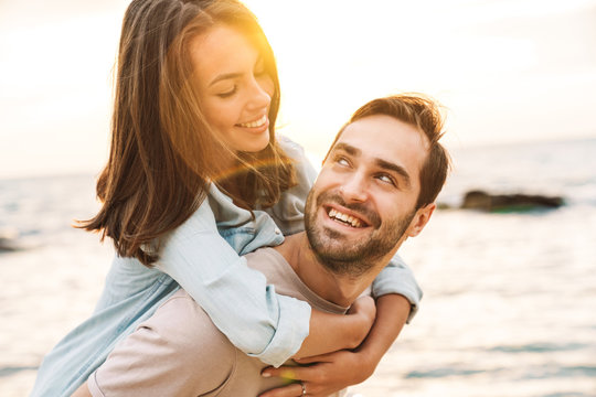 Image of young man giving piggyback ride and looking at beautiful woman