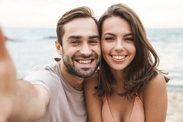 Photo of joyful young couple smiling and taking selfie photo