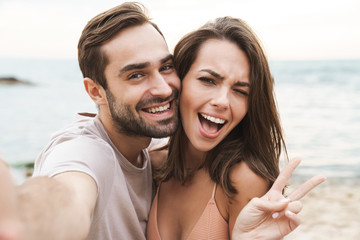 Photo of smiling young couple gesturing peace sign and taking selfie