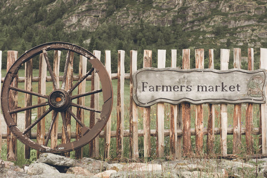 Sign and cartridge wheel with wooden fence and natural backdrop.