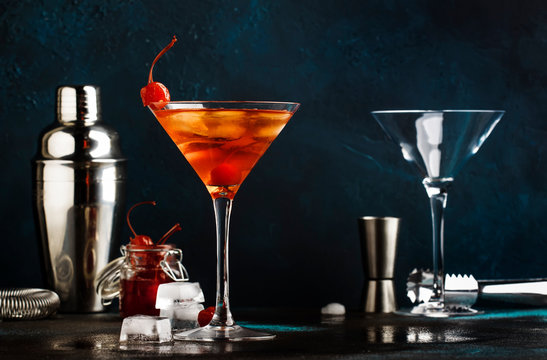 Classic alcoholic cocktail Manhattan with bourbon, red vemuth, bitter, ice and cocktail cherry in glass, gray bar counter background, place for text, selective focus