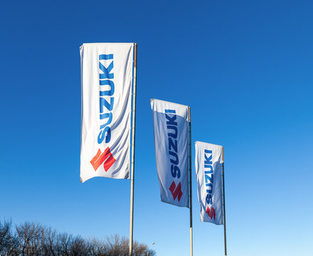 The flags with emblem Suzuki over blue sky