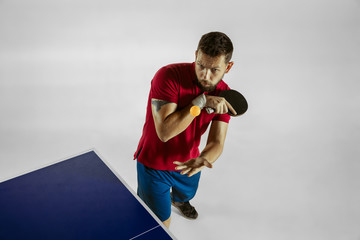Wall Mural - Young man plays table tennis on white studio background. Model in sportwear plays ping pong. Concept of leisure activity, sport, human emotions in gameplay, healthy lifestyle, motion, action, movement