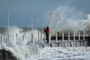 Girl makes extreme selfie on the pier against the background of waves with a risk to life in a storm.