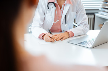 Close-up of doctor taking notes while having appointment with patient