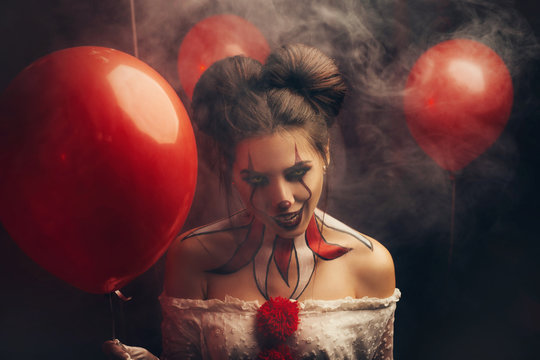 Creepy beautiful woman in the image of a scary clown. Carnival outfit white dress with red buboes. Close-up portrait. Bloody smile, obsessed with crazy eyes. Creative art makeup. Halloween celebration