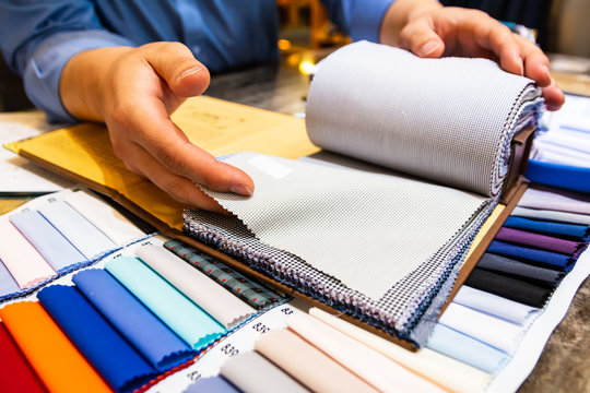 tailor choosing a fabric in swatch for his customer