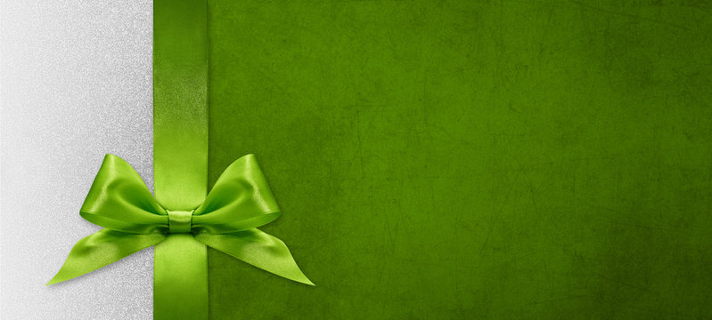 christmas gift card with green ribbon bow on green and silver background, copy space template