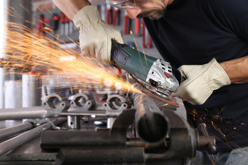 man work in home workshop garage with angle grinder, goggles and construction gloves, sanding metal makes sparks closeup, diy and craft concept