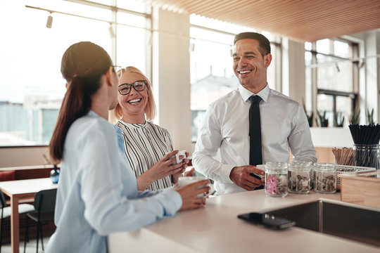 Laughing businesspeople talking during their office coffee break
