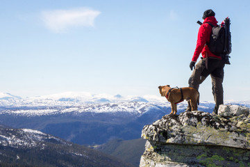 Man and dog standing on steep hillside and looking towards the snowy peaks of Jotunheimen in Norway. Staffordshire bullterrier, hiking, trekking, lifestyle, rondane and Norway concept. Wall mural