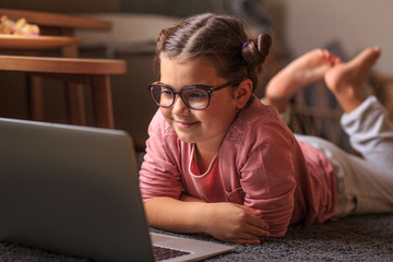 Young smart baby girl playing at home and using laptop.