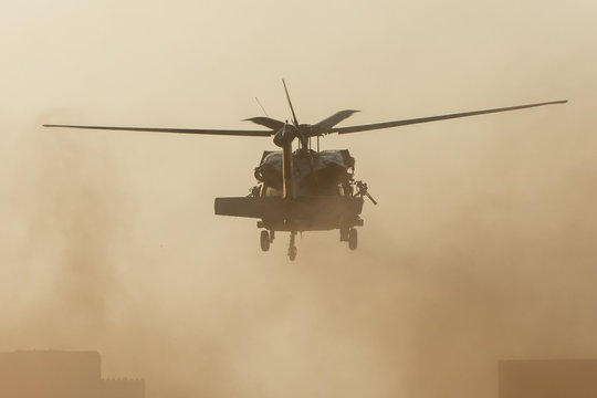 Military chopper takes off in combat and war flying into the smoke and chaos and destruction. Military concept of power, force, strength, air raid. Portrait View.