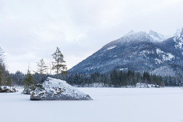 partly frozen lake hintersee with snow in winter and rocks