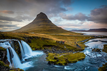 Foto auf Leinwand Insel The picturesque sunset over landscapes and waterfalls. Kirkjufell mountain, Iceland
