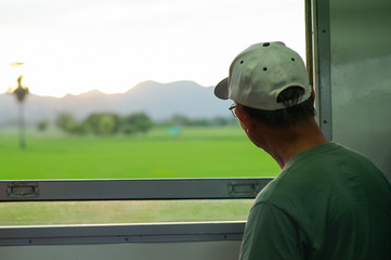 Closeup back portrait of old man with casual clothes and eyeglasses sits in moving train and looks out the window to landscape view in sunset vibe background