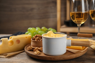 Pot of tasty cheese fondue and products on wooden table