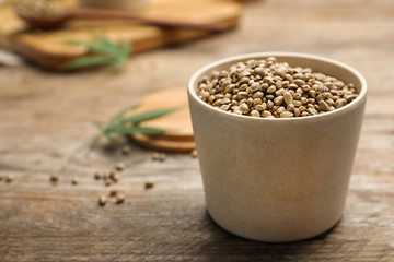 Organic hemp seeds in bowl on wooden table