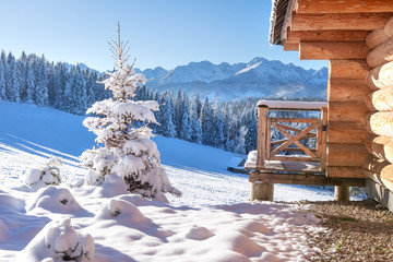 Photo sur Aluminium Bleu ciel Skiing resort in snowy mountains on clear sunny day. Winter nature landscape with wooden house and Christmas trees in mountain valley. Ski season
