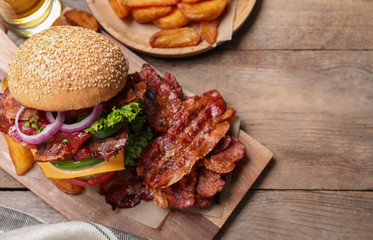 Composition with juicy bacon burger on wooden table, above view. Space for text
