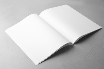 Blank open book on light grey stone background. Mock up for design
