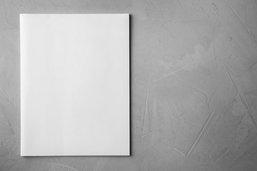 Blank book on light grey stone background, top view. Mock up for design