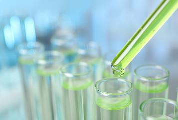 Fototapete - Dripping liquid into test tube on blurred background, closeup. Laboratory analysis