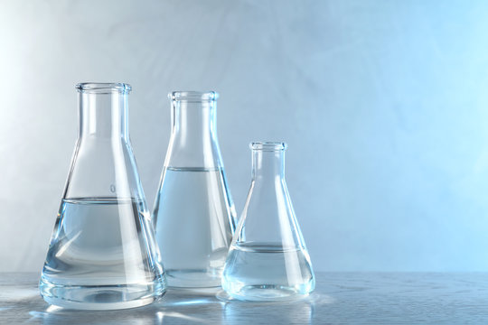 Laboratory glassware with liquid samples for analysis on table against toned blue background, space for text