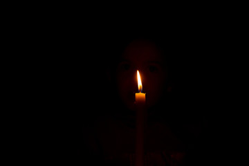 burning candle in absolute darkness