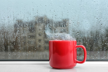 Cup of hot drink on white windowsill. Rainy weather