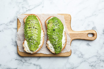 Tasty avocado sandwiches on white marble table, top view