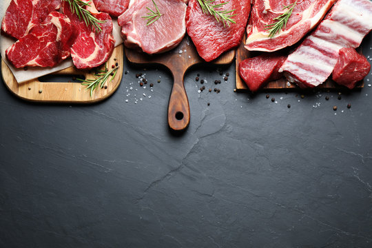 Flat lay composition with fresh meat on grey table. Space for text