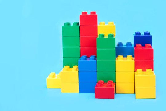 Bar graphs plastic building blocks toy bricks on blue background.