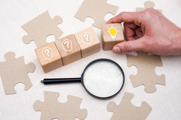 Concept idea and search innovation. Hand picked wooden cube block with head human symbol, question and idea bulb icon.