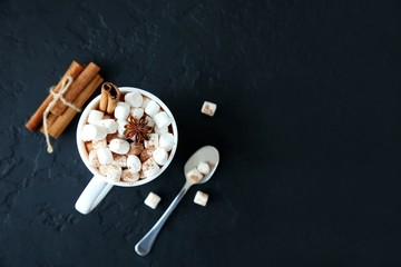 Mug of hot chocolate with marshmallows on a dark background. Top view, copy space.