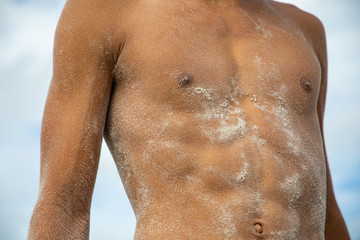 Male Body on the beach covered with Sand