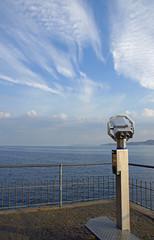 Aussichtspunkt mit Fernglas an einem See im November unter blauem Himmel mit Cirruswolken