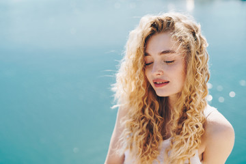 tender curly blonde covering her eyes and opening her mouth slightly enjoys the rays of the sun against the ocean