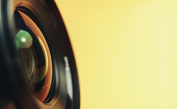 Beautiful camera lens with yellow and pink light of glass on a black background...