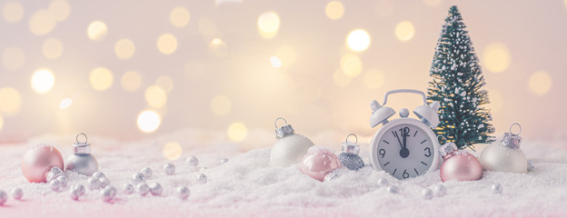 Pink and White glass Christmas balls with an alarm clock on a snowflake and lights background, toned, banner Wall mural