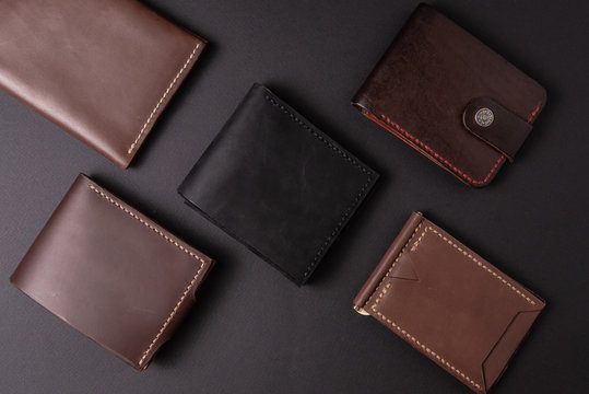 leather wallets on a black background with space for an inscription. Leather craft concept.