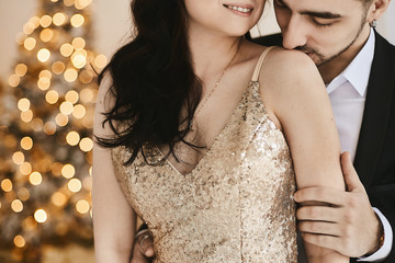 Sexy passionate couple celebrating Christmas together. Attractive woman in gold evening dress and handsome bearded man in a suit posing in an interior with New year festive lights on the background. Wall mural