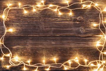 Vintage Christmas wooden background with led lights border.