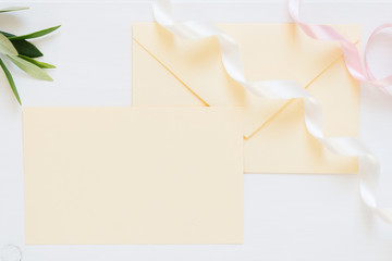 blank cream-colored envelope with ribbons, mock up for romantic invitations, wedding design